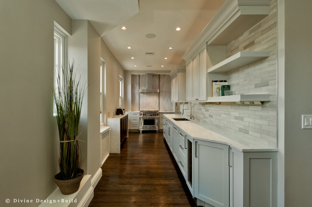 Transitional style kitchen with grey stone subway tile backsplash. Off white shaker cabinets, and wolf appliances.
