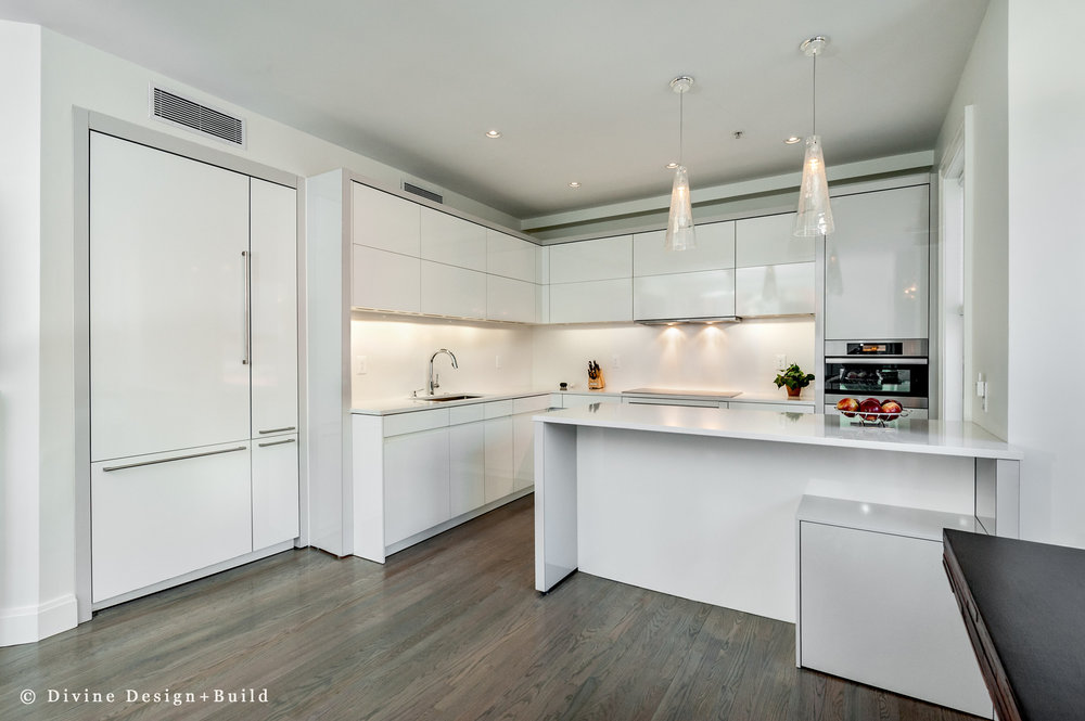Modern leicht kitchen and family room. High gloss white handleless cabinets. .