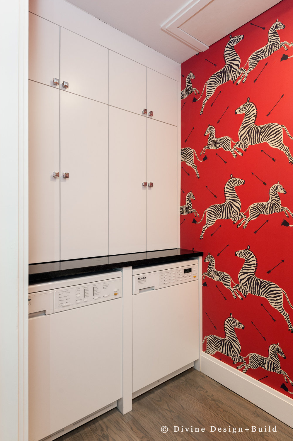 Modern laundry room with red wallpaper and zebras.