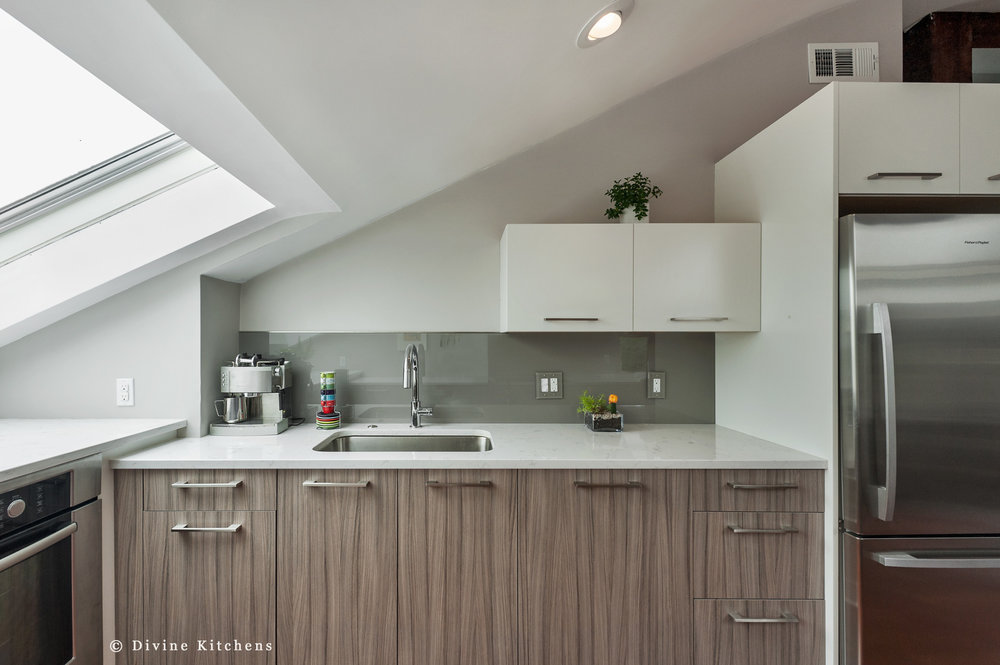 Sleek two-tone kitchen design with leicht modern cabinets. Grey oak cabinet fronts. Large skylight.