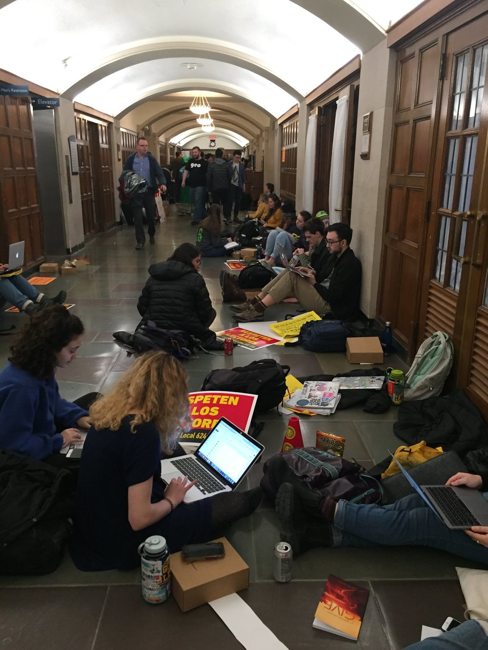 "Hall at the Michigan League full of students sitting against the walls and in the middle of the floor with ""Respect the Lecs"" signs, working on laptops and talking."