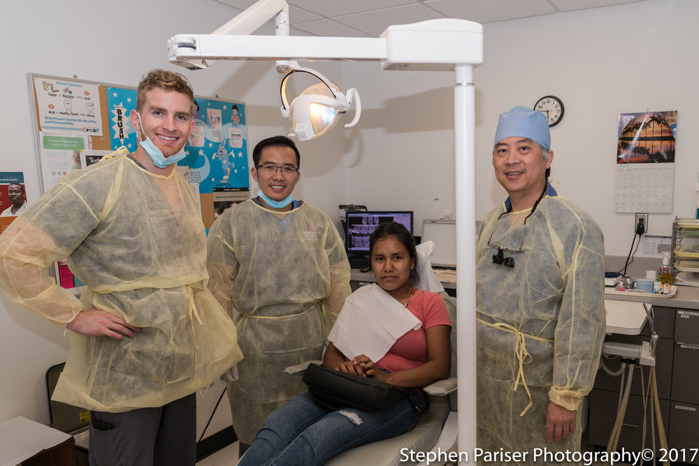 Dentists pose next to a patient at the Physicians Free Clinic, Photo by Stephen Praiser, 2017