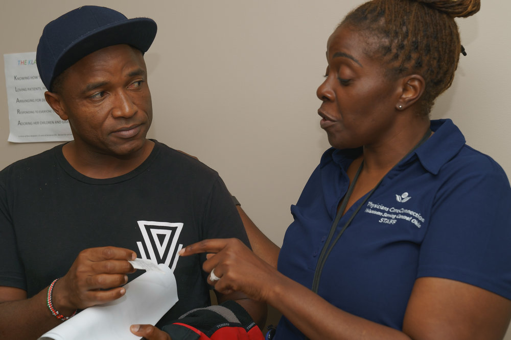 Isi Green, Executive Director of PCC, assists a patient at the Physicians Free Clinic