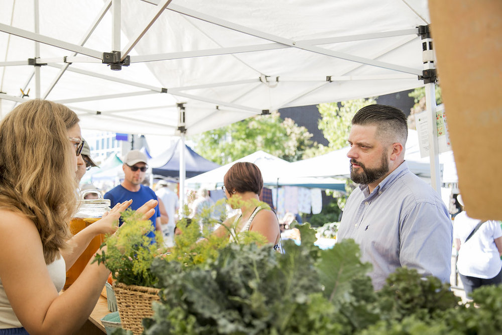 Jason visiting with an area farmer at the Saturday Market about the challenges and opportunities for those involved in supplying local food.
