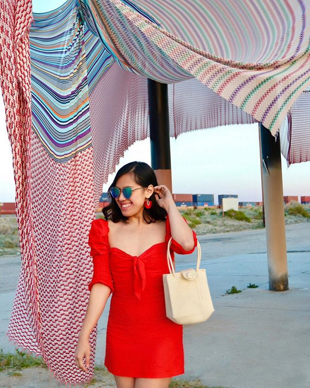 "Get lost in the #desert 🌵 with me... . Because this year is @_desertx; this exhibit happens biennially with art scattered across the desert 🐫. . Go experience bigger than life art installations from Palms Springs 🌴 to Salton Sea 🌊 . My #favorite is ""Halter"" by @ernatmack. . . Plus this red ❤️ statement dress from @vixens_vice was perfect for this #adventure. (Want it?! Click the link in my bio 😉) . . . #flashbackfriday #fashionfriday"