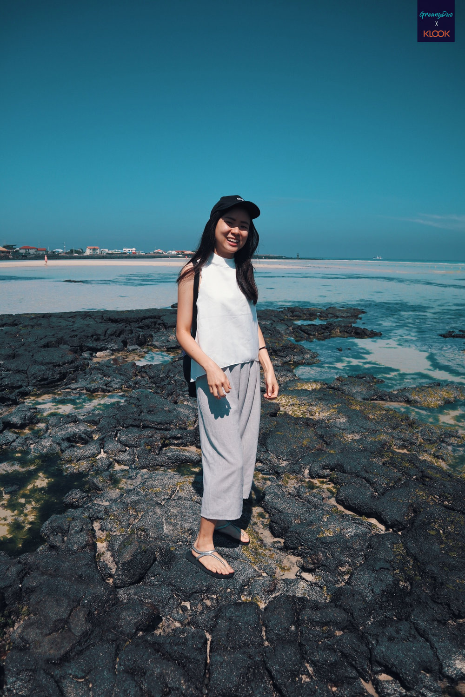 jenny standing on black volcanic rock at hyeopjae beach