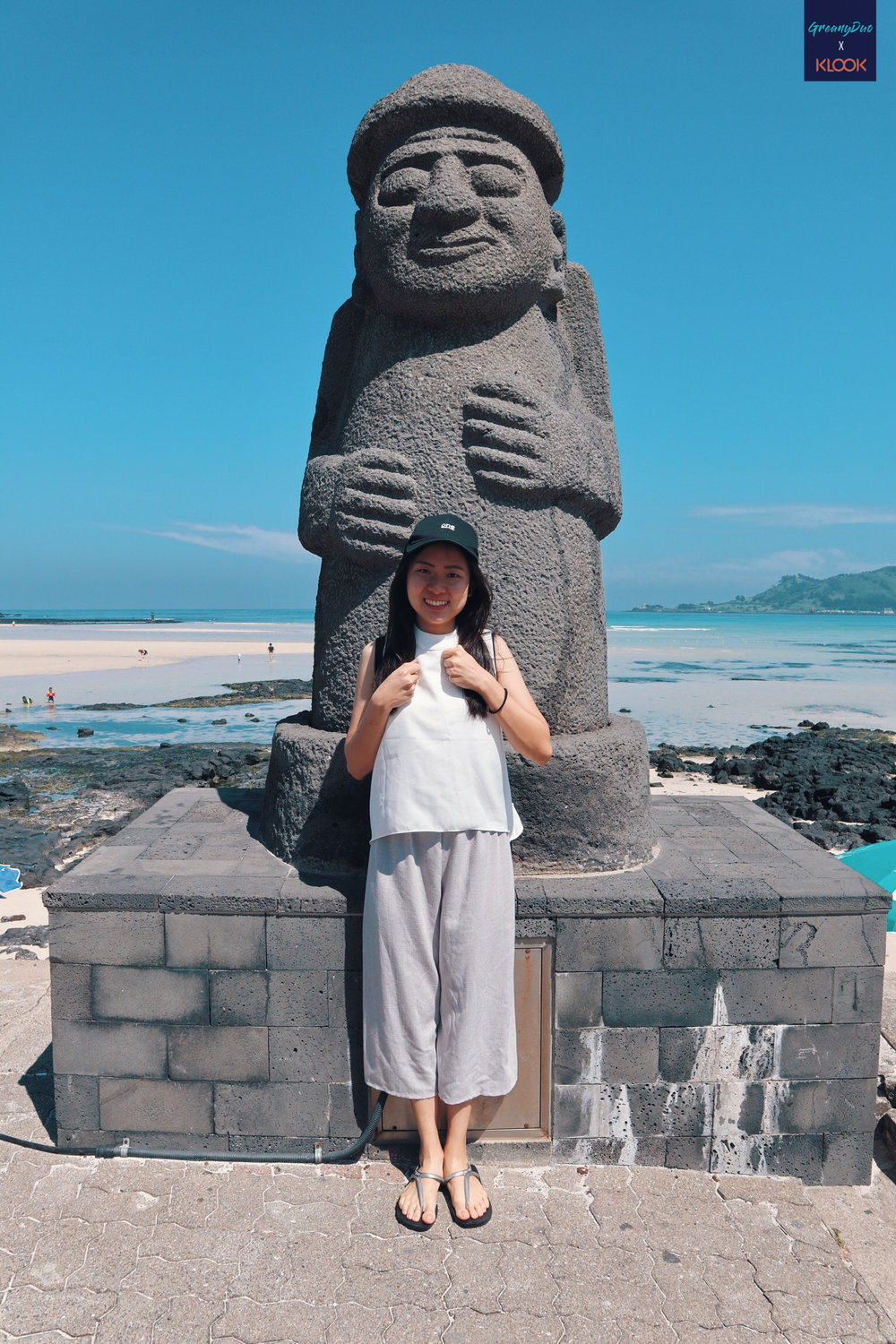 jenny posting with jeju's dol hareubang at hyeopjae beach