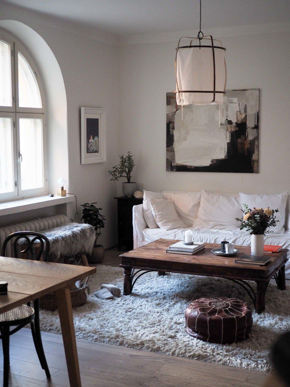 Lempiasioitani olohuoneessa: Marianne Niemisen maalaus ja Gervasonin Ghost -sohva. Ay Illuminaten valaisimen ja Normann Copenhagenin ruokapöydän olen ostanut ystäviltä. Kaappi, tuolit, sohvapöytä ja koriste-esineet kirppiksiltä. Penkki on Granitista ja vuosia vanha matto aikoinaan Stockmannilta.