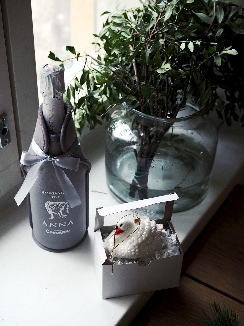 Takuuvarma pikkujoululahja: pullo kuohuvaa ja ajatuksella valittu, kaunis joulukoriste. Neopreenistä tehty pakkaus pitää viinin kylmänä pidempään.