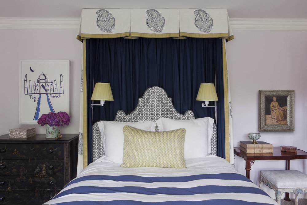In a guest room, a headboard upholstered in a   Holland & Sherry  textile is framed by bed hangings of   Pintura Studios   and   Loro Piana   fabrics. The sconces are by   Hinson and Co.  , the bedding is by   Frette  , and the walls are painted in Benjamin Moore's   Peace and Happiness  .