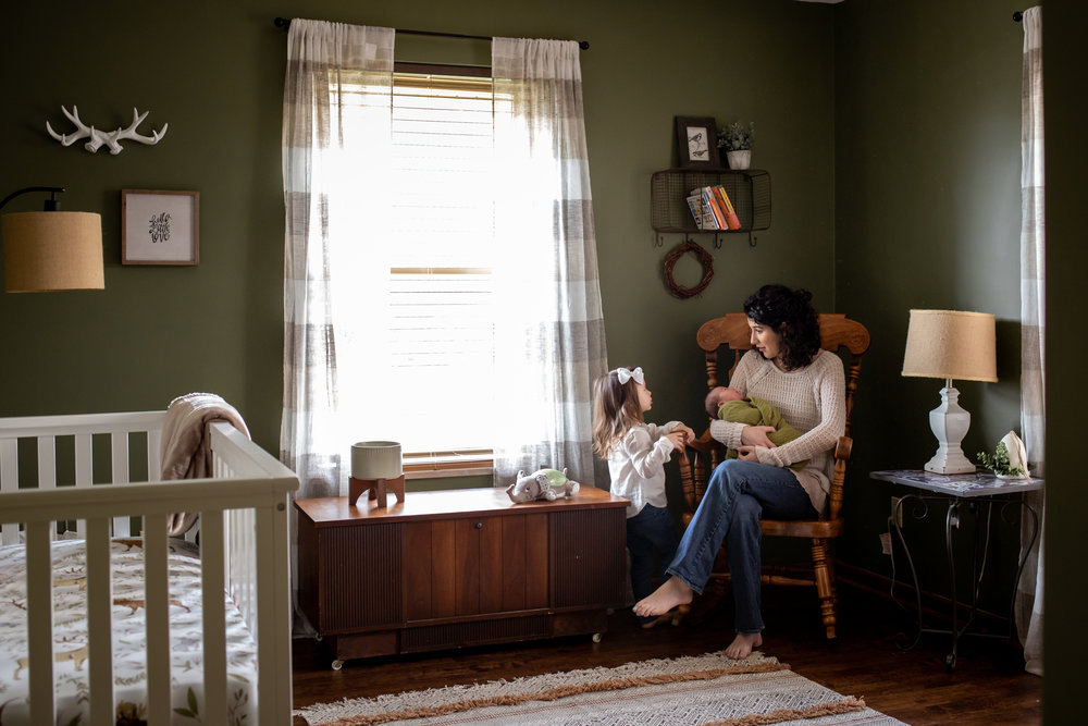 mother holds her newborn son in his nursery in Maryville while talking to her toddler daughter during their lifestyle photo session