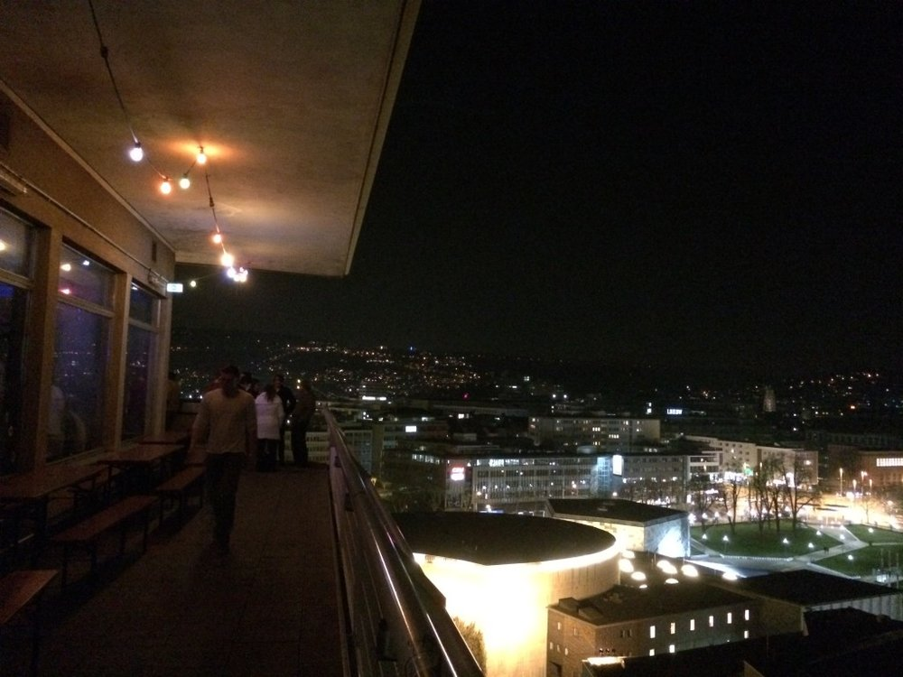 On a terrace of a rooftop penthouse(?) of a dorm building that they somehow turn into a bar/club on Wednesdays