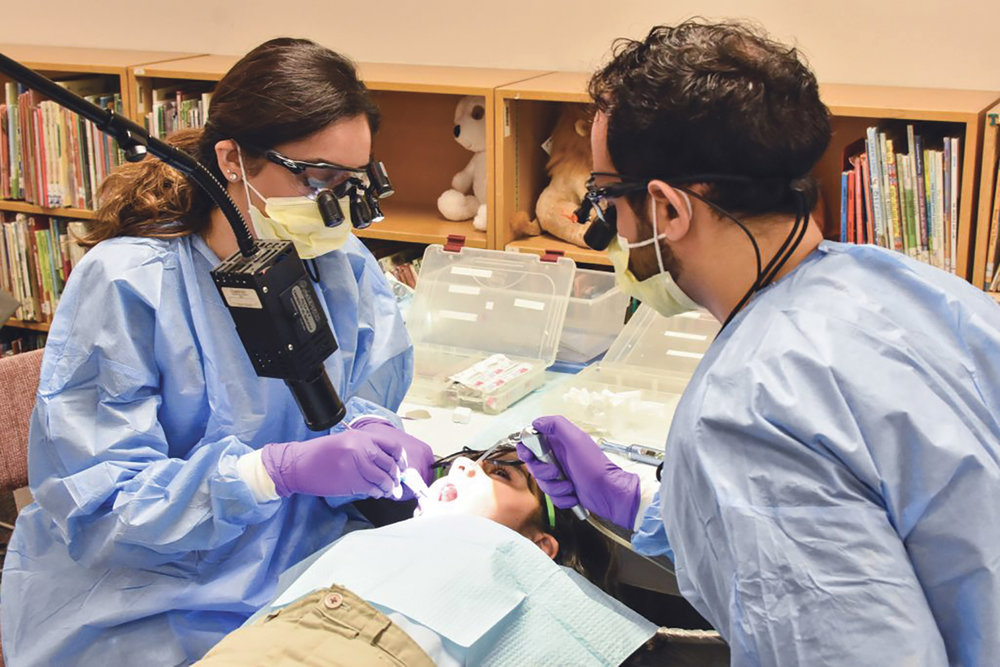 Students from Texas A&M College of Dentistry, Nida Suleman (left) and Shahriar Soroushi (right) provides a third grader free sealants in the library of Thomas Haley Elementary, in Irving. (Photo: Rachel Hawkins/North Dallas Gazette)