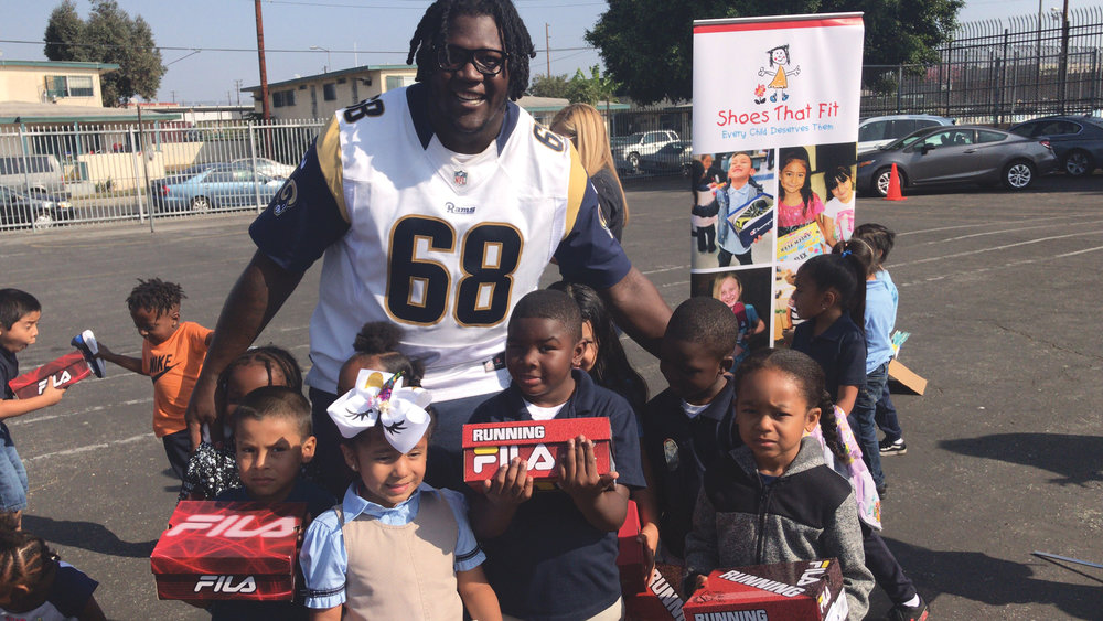 Jamon Brown gifting Holmes Ave Elementary students new shoes in October 2018. (whatsgoodinsports.com photo)