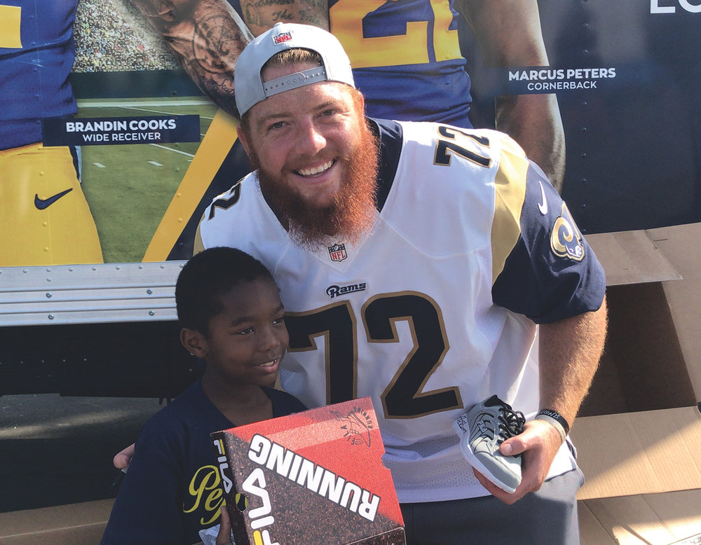 Aaron Neary gifting a Holmes Ave Elementary student new shoes in October 2018. (Whatsgoodinsports.com photo)