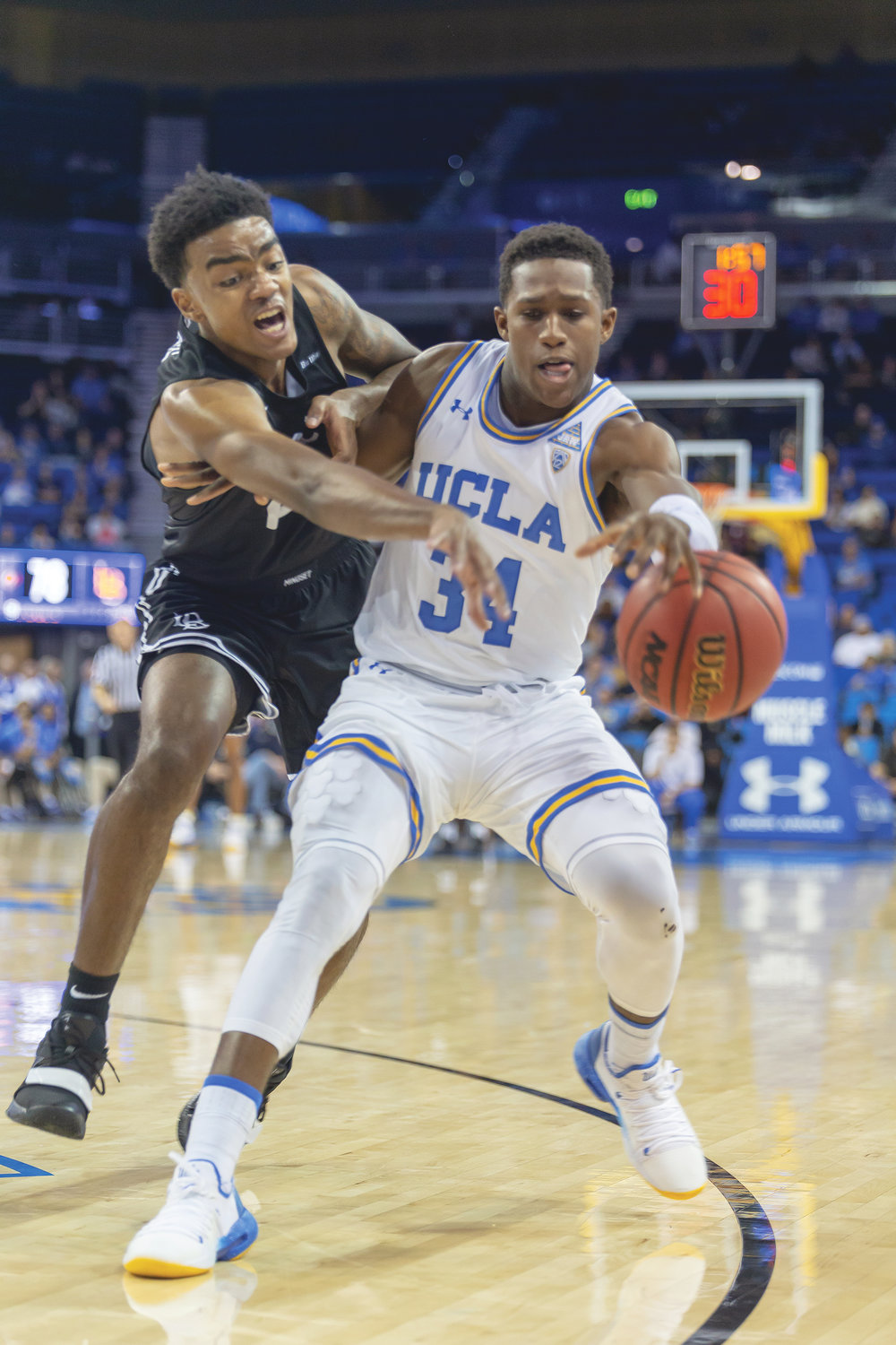 Former Bishop Montgomery and current UCLA freshman guard David Singleton (right) fends off Long Beach State sophomore Jordan Roberts (left). The Bruins went on to win 91-80 Friday night in Pauly Pavilion. (Lenny Washington/@Ucla Housing photo)