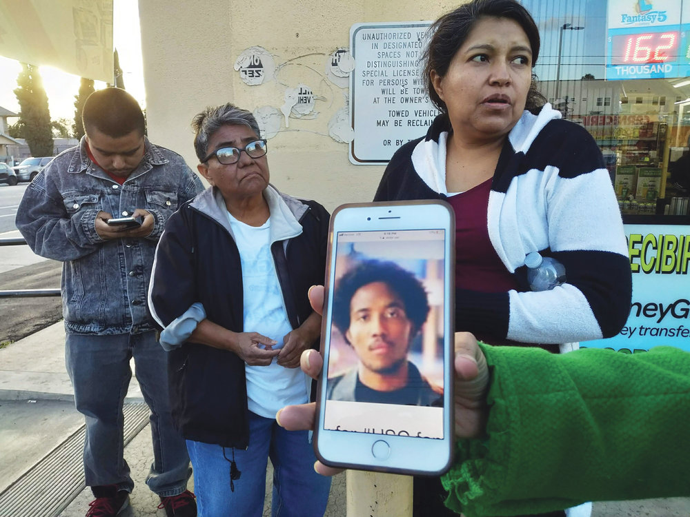 Neighbors react as they look at a cellphone picture of University of Southern California student Victor McElhaney, shown by a television reporter near the scene of a crime in Los Angeles, Sunday, March 10, 2019. McElhaney, the son of an Oakland, Calif., city councilwoman, was shot and killed in an apparent robbery attempt near the USC campus, officials said. (AP Photo/Damian Dovarganes)