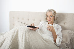 senior-woman-watching-tv-having-coffee-bed-35914959