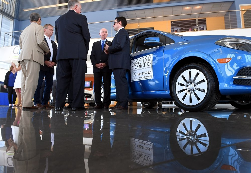 Connecticut DEEP Commissioner Rob Klee, right, talks with Congressman Joe Courtney, center, State Senator Paul Formica, and local automotive dealer representatives after announcing DEEP's CHEAPR (Connecticut Hydrogen and Electric Automotive Purchase Rebate) program, creating financial incentives for purchasing electric vehicles, during a press conference at Carriage House Mercedes in New London Tuesday, June 30, 2015. (Tim Cook/The Day)