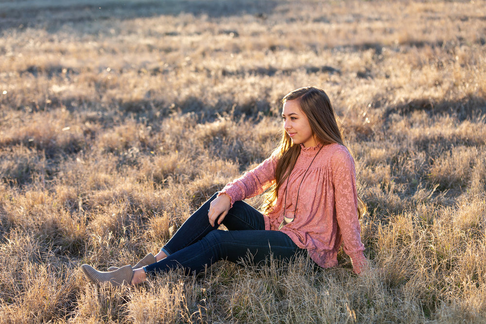 Senior-girl-sitting-grassy-field.jpg