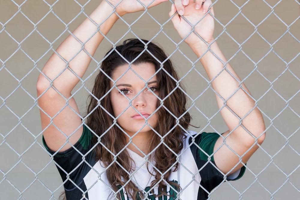 Senior-girl-softball-dugout-fence.jpg