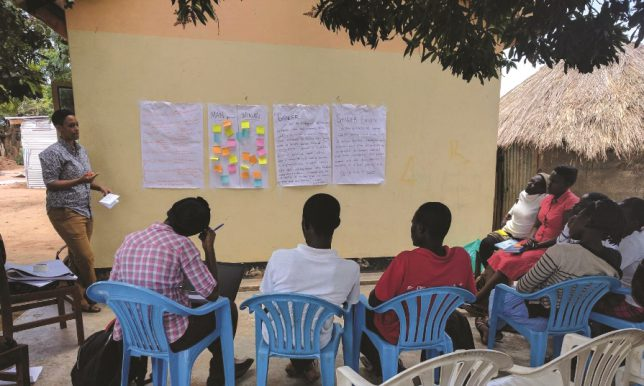 Julia Jordan leads a workshop with student interns in Soroti, Uganda, to write down the gender norms, roles or expectations of women and men in their communities.