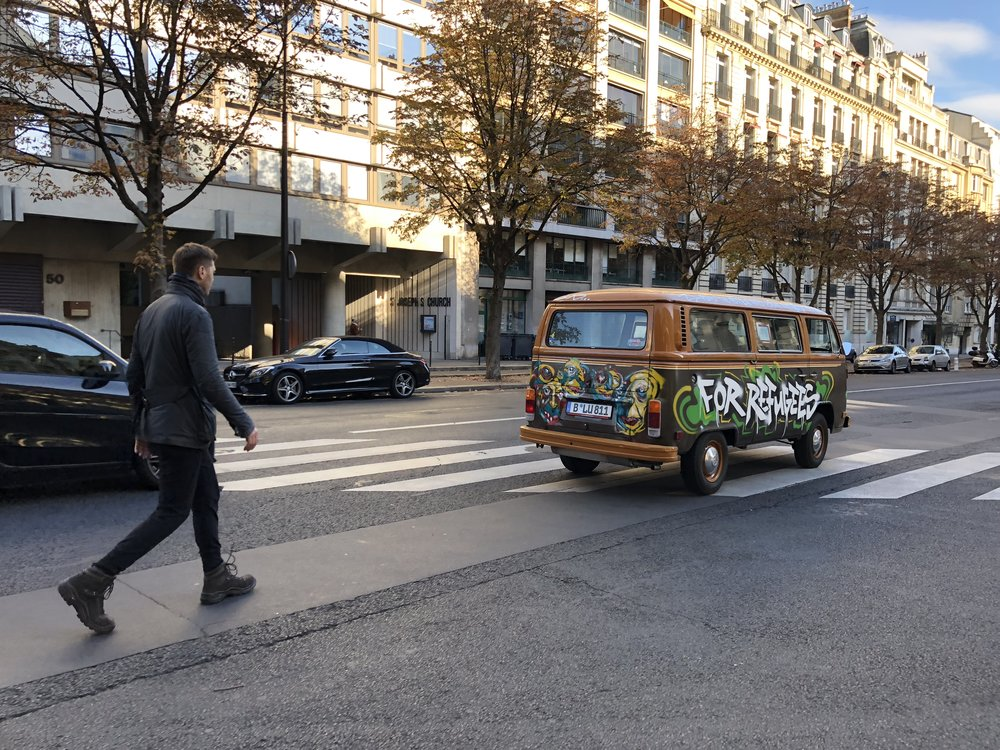 Grig walking behind the vw bus in Paris.JPG