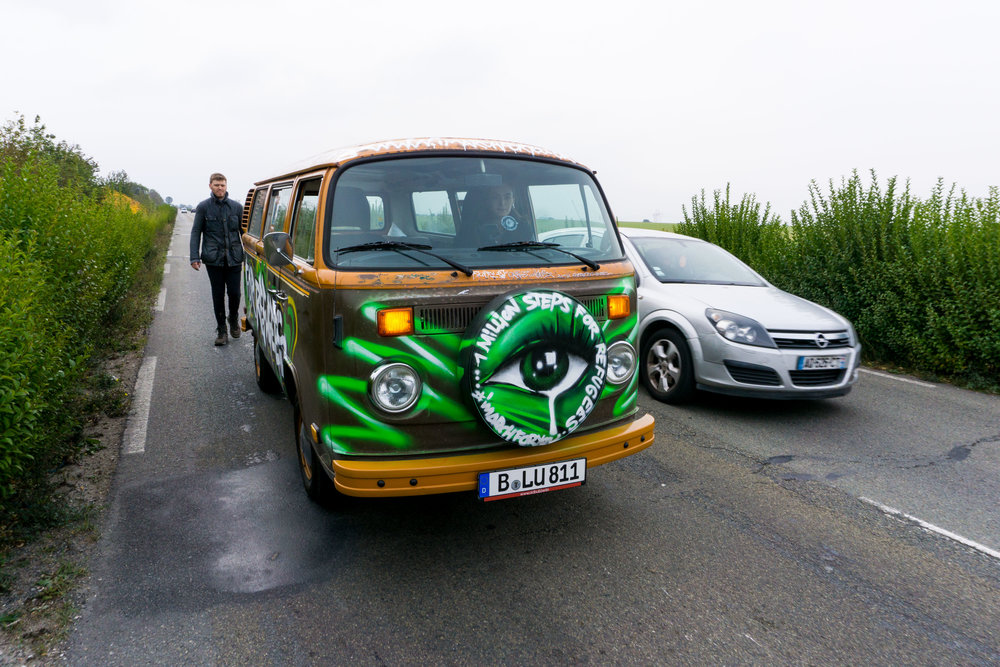Grig-walking-behind-vw-bus-as-car-takes-over.jpg