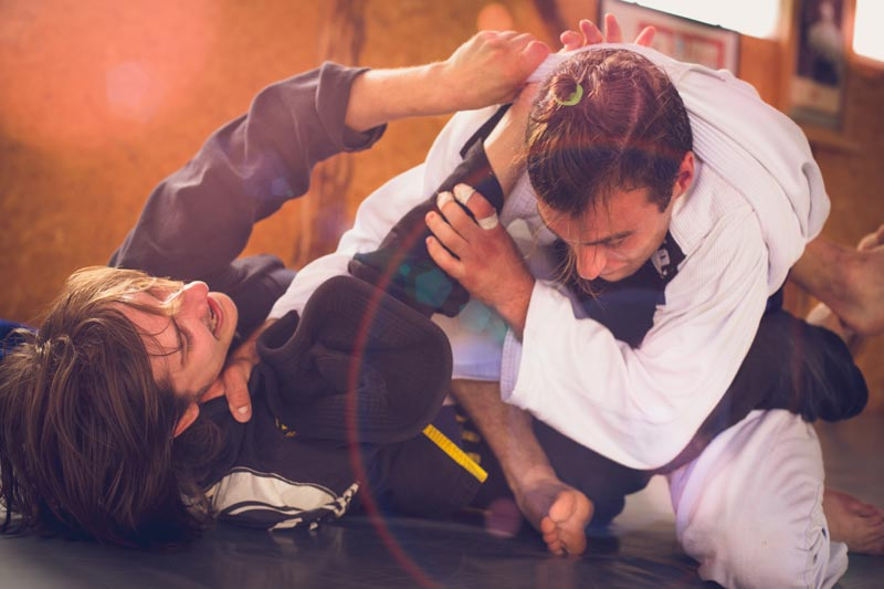 how-bjj-works-man-in-white-gi-in-closed-guard-iStock-589547910.jpg