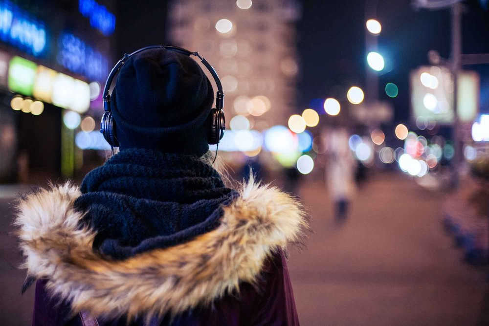 how-bjj-works-woman-walking-in-city-at-night-listening-to-podcast-iStock-876587286.jpg