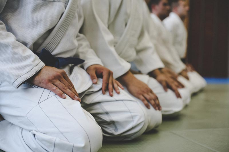 how-bjj-works-students-at-bjj-gym-line-up-in-rank-iStock-946060408.jpg