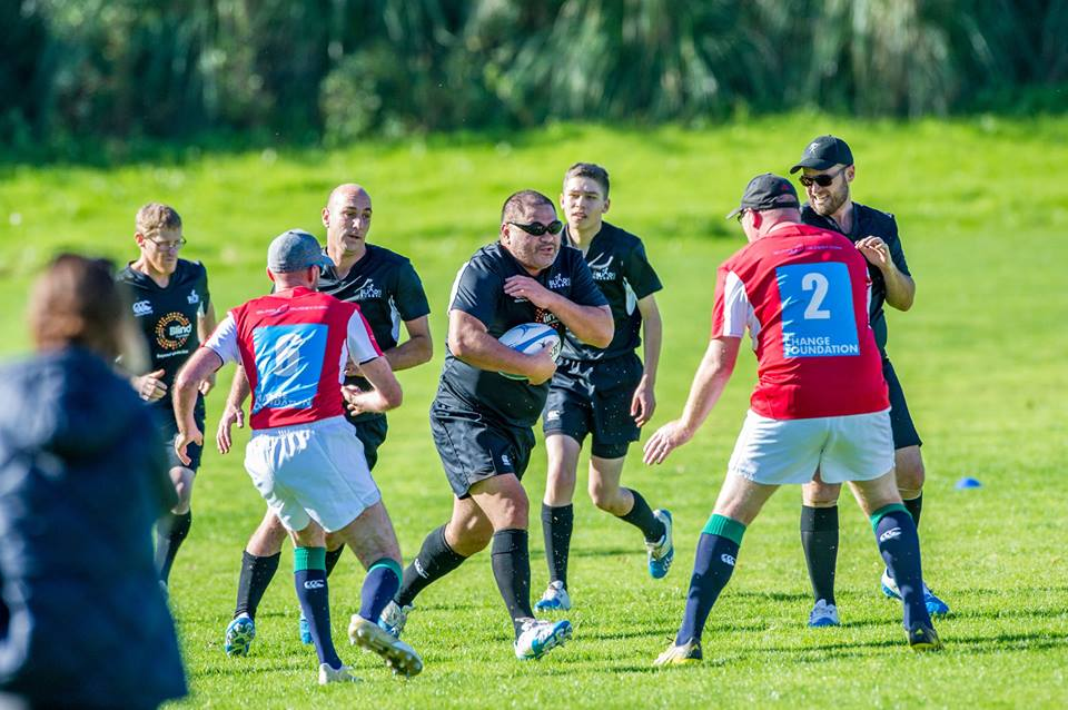 NZ blind rugby player holding ball runs forwards while Blind Lions players come in to defend
