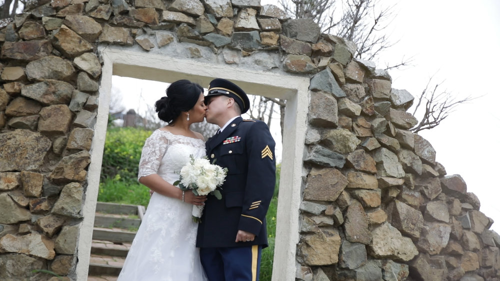 Wedding Photography and Videography Catalina Island - Hotel Metropole - Groom in Army attire kissing bride in front of a stone wall.