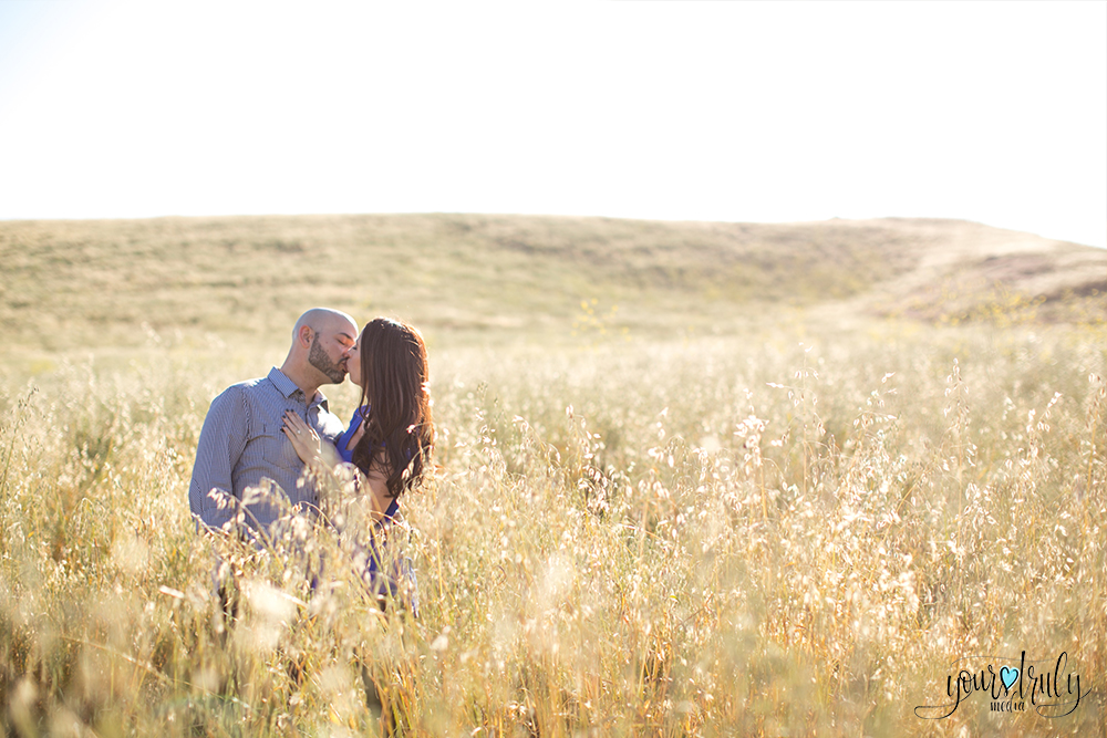 Engagement Photography Services in Orange County, CA - Man kissing his future bride in a golden field of wheat.