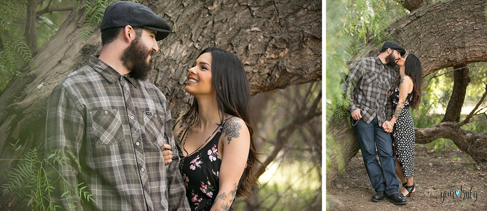 1-year anniversary photography feature - Couple standing by a large tree and kissing.