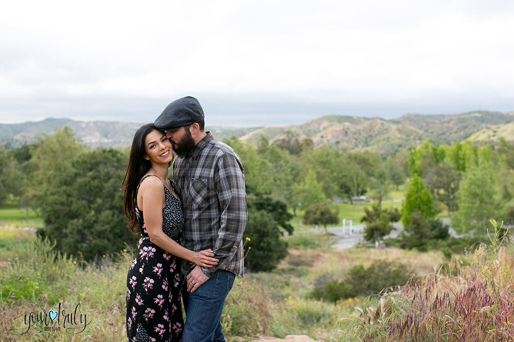 1-year anniversary photography feature - Couple standing on higher ground overlooking trees with mountains in the background.