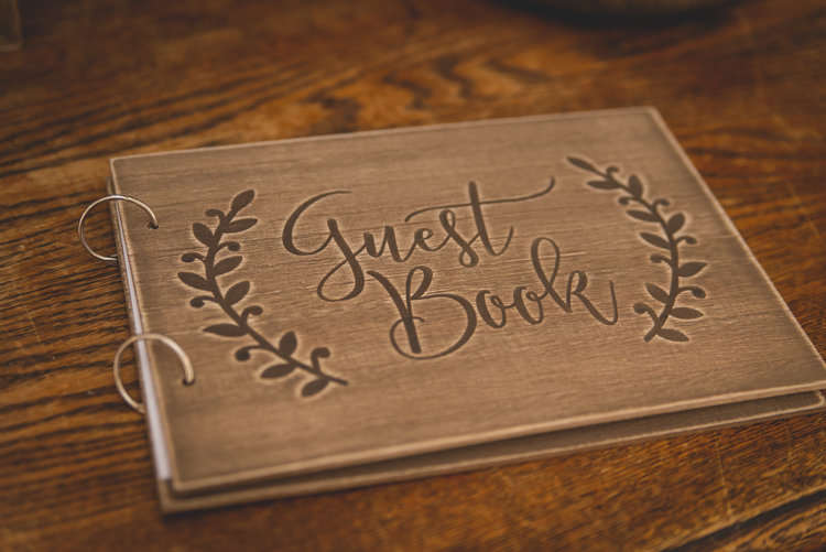 A wooden wedding guest book decorated with engravings.