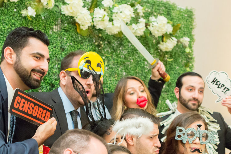 Wedding guests holding up props for a photo booth.