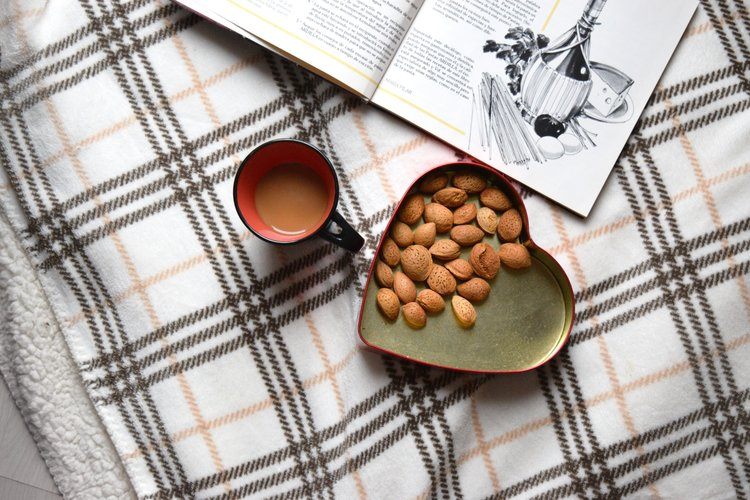 Almonds in a heart-shaped container, a coffee mug, and a cookbook on a quilt.