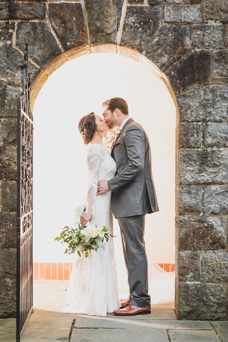 A bride and groom kissing in the stone doorway of an 19th century cathedral.