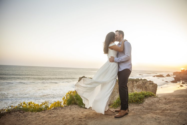 Unforgettable Save the Date Ideas - Engagement photography of a couple kissing on the beach.