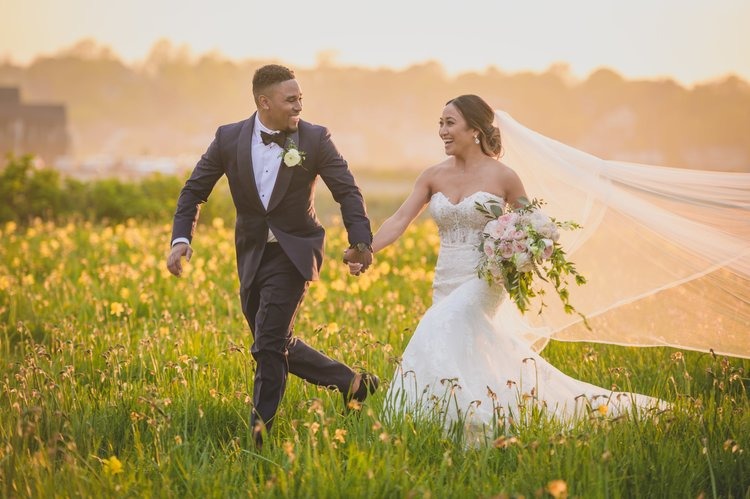 Ways to keep guests cool at your warm-weather wedding - Bride and groom holding hands while running through a field of flowers.