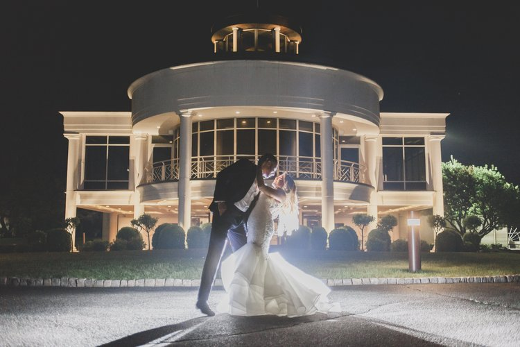 Ways to keep guests cool at your warm-weather wedding - Evening photograph of a bride and groom in front of their venue with a spotlight shining on them as the groom dips the bride for a kiss.
