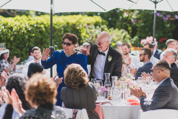 Last Minute Checklist: Things to Know Before Your Outdoor Wedding - An older couple greet guests as they arrive at the wedding reception.