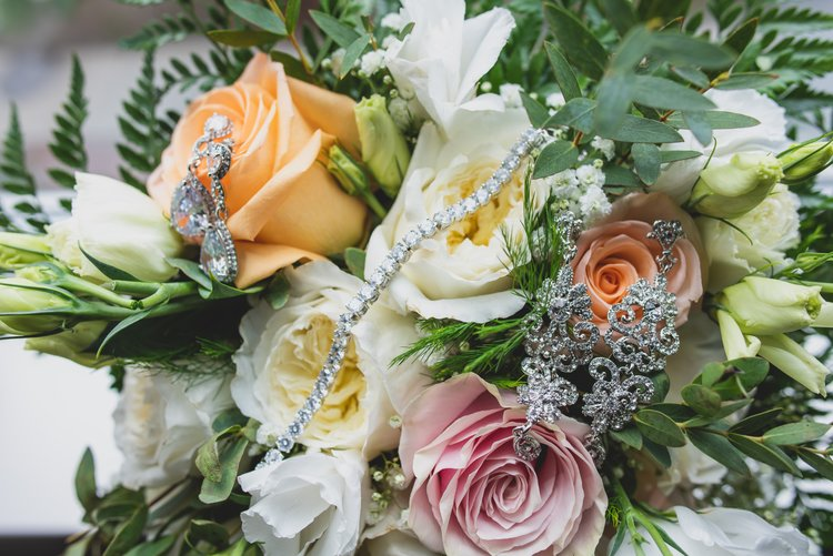 A bouquet of roses adorned with the brides jewelry.