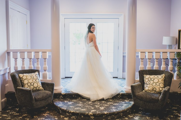 A bride showing off her wedding dress in a purple hued room.