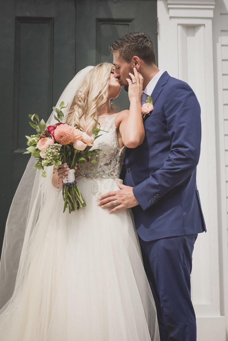Bride and groom kiss in front of deep green, moody-hued accent door.