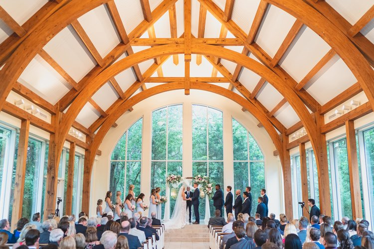 Wedding ceremony in a chapel with wooden arches decorating the high vaulted ceiling.