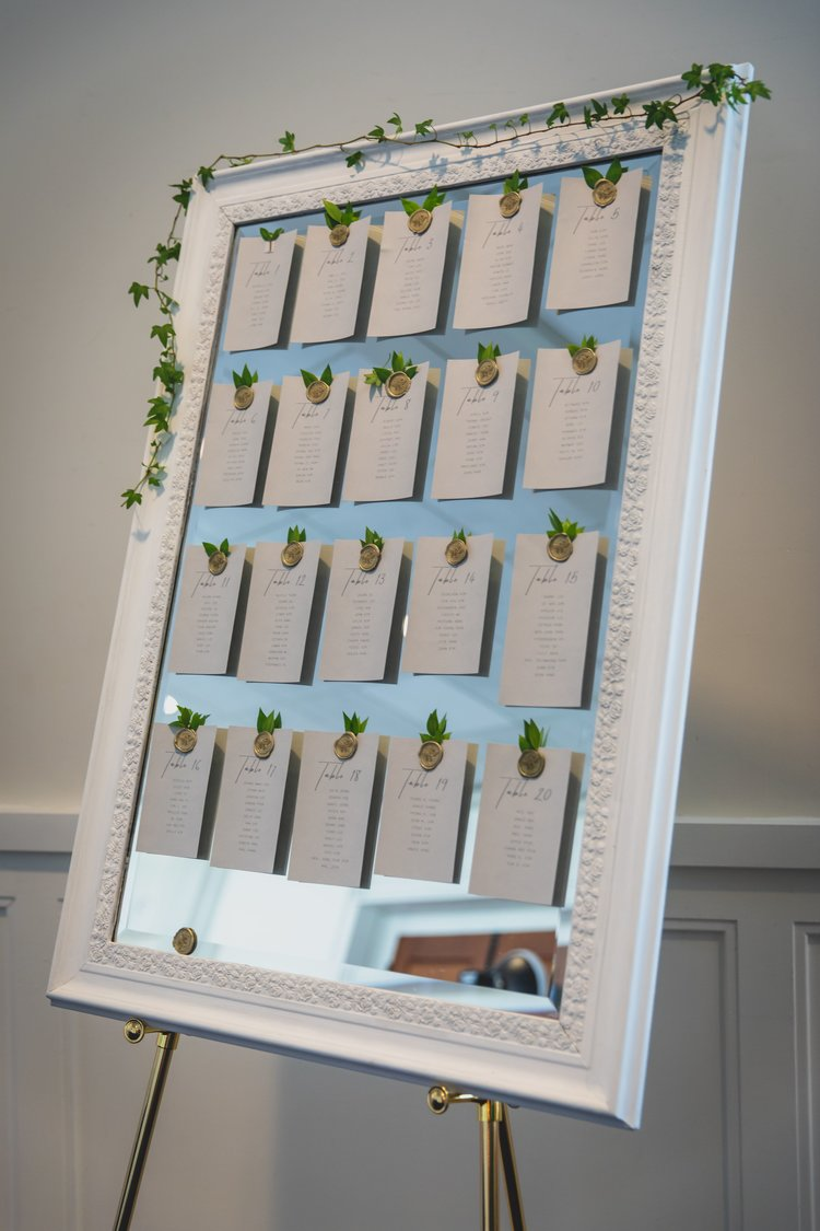 Wedding seating charts displayed on mirror with a white wooden frame.