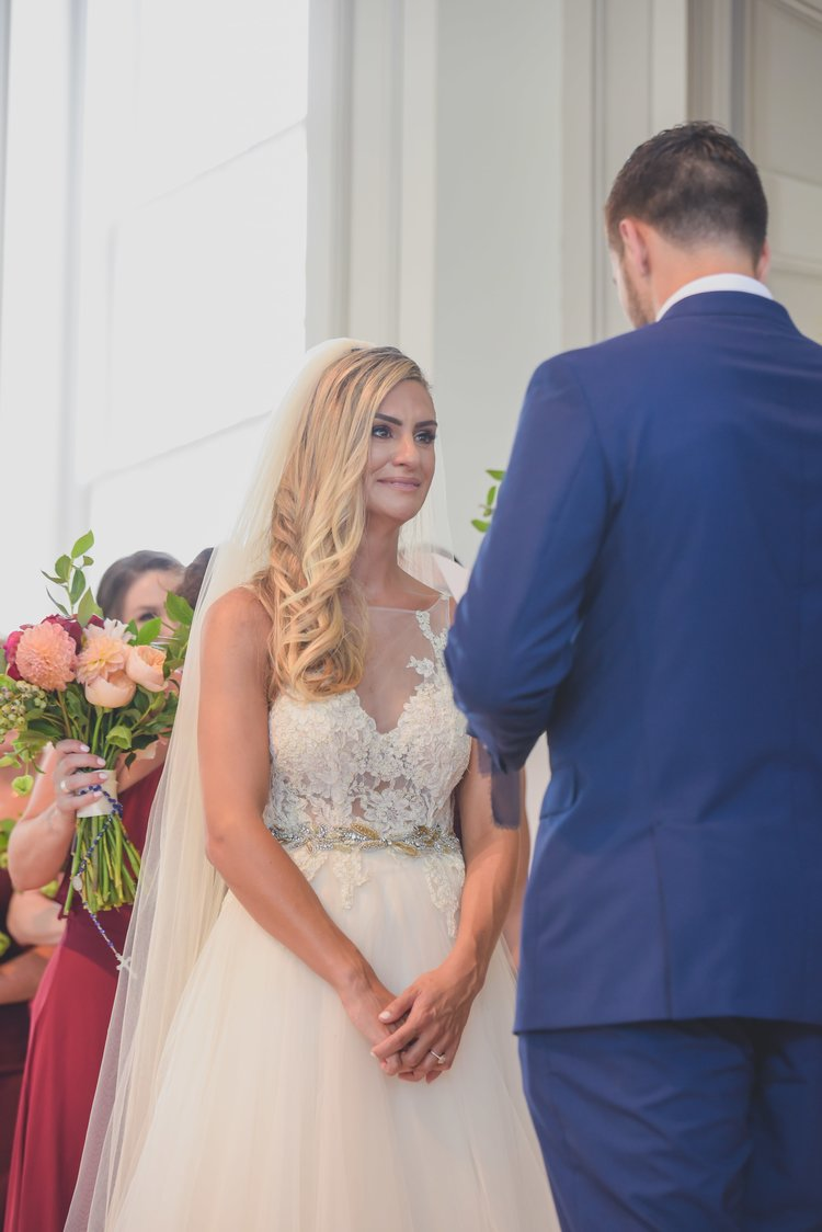 A bride crying as the groom reads her his personalized wedding vows.